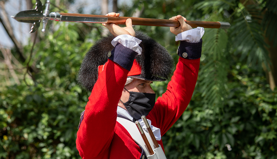 a new soldier in training for the united states army old guard fife and drum corps raises his spear over his head in an exercise