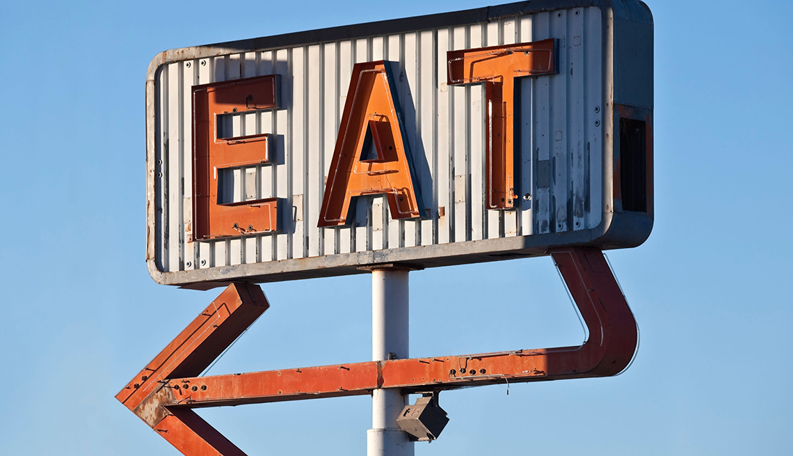antique road sign that says eat