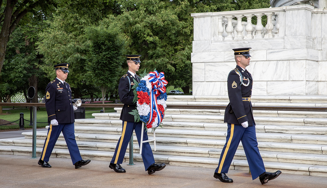 three soldiers performing a wreath laying ceremony at the tomb of the unknown soldier in arlington cemetary
