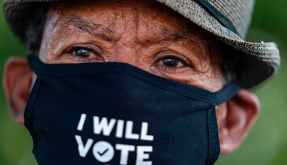 A man wearing a hat and mask with the words I will vote on it