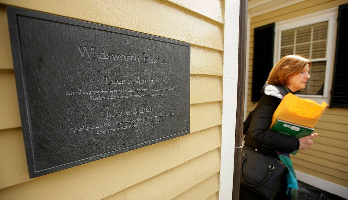 Una transeúnte camina cerca de una placa puesta en Wadsworth House en el campus de la Universidad de Harvard