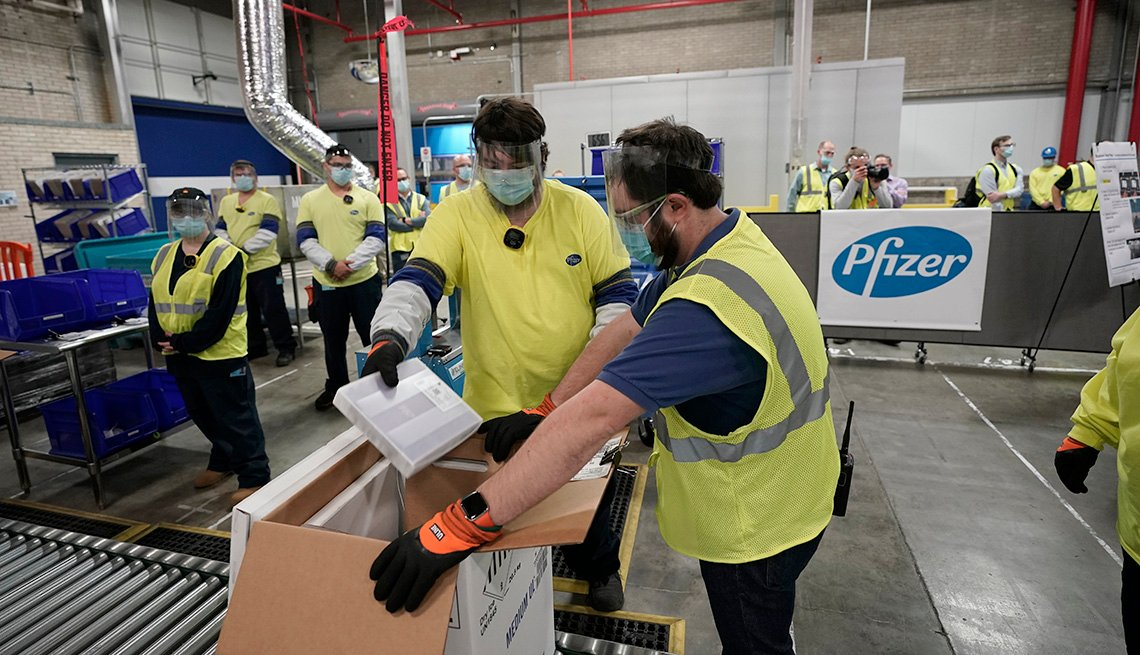 item 2 of Gallery image - workers pack boxes of covid nineteen vaccines at a pfizer plant