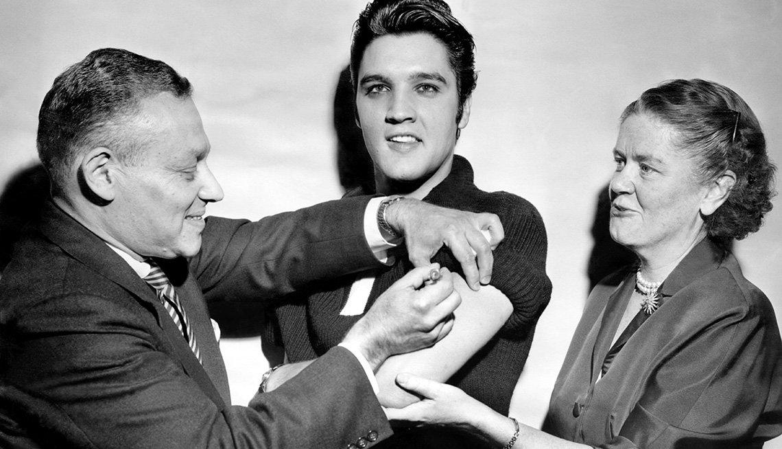 item 5 of Gallery image - La comisionada de salud de la ciudad, Leona Baumgartner, sostiene el brazo de Elvis Presley mientras se le administra la vacuna contra la polio