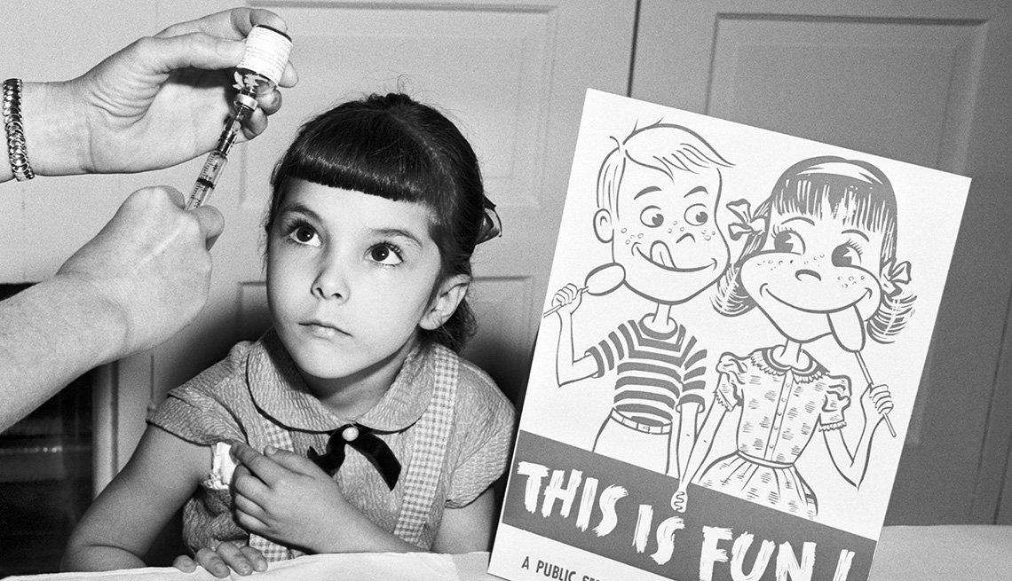 item 7 of Gallery image - Una niña se prepara para recibir la vacuna contra la polio
