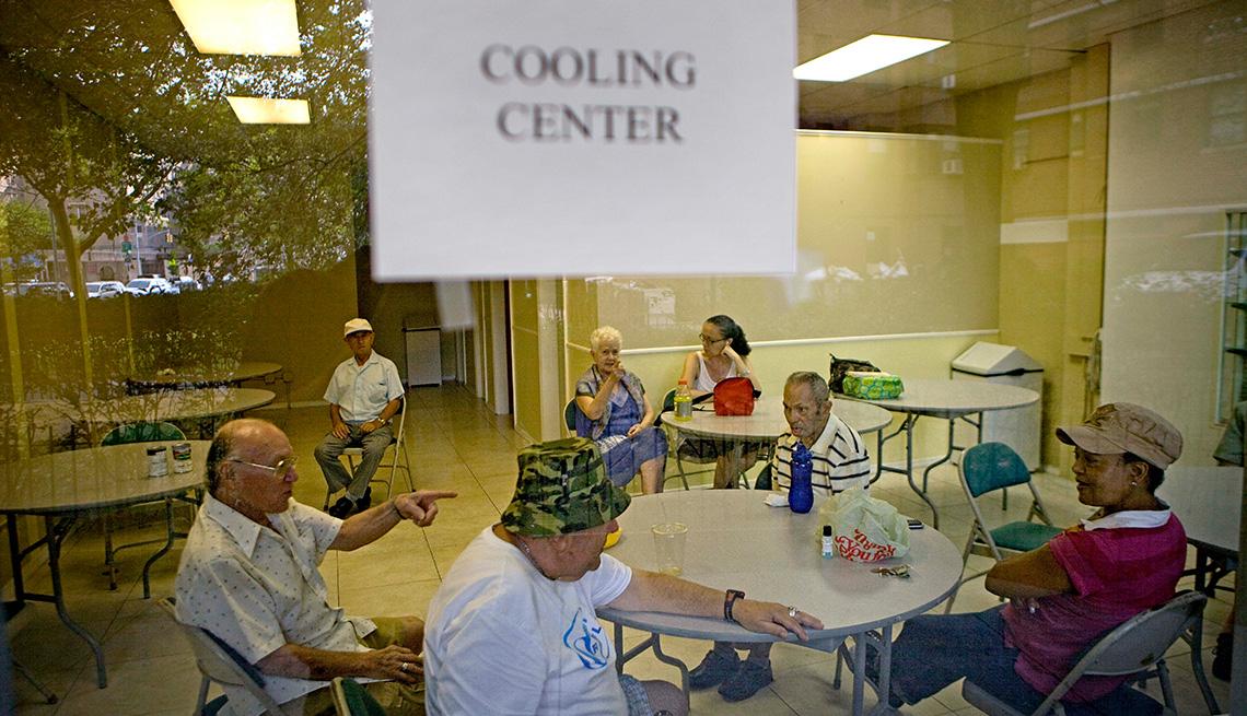 Personas mayores sentadas dentro de un centro de enfriamiento
