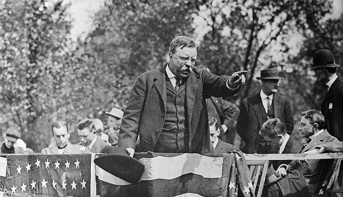 Theodore Roosevelt standing on a podium pointing into the crowd during a campaign rally speech.