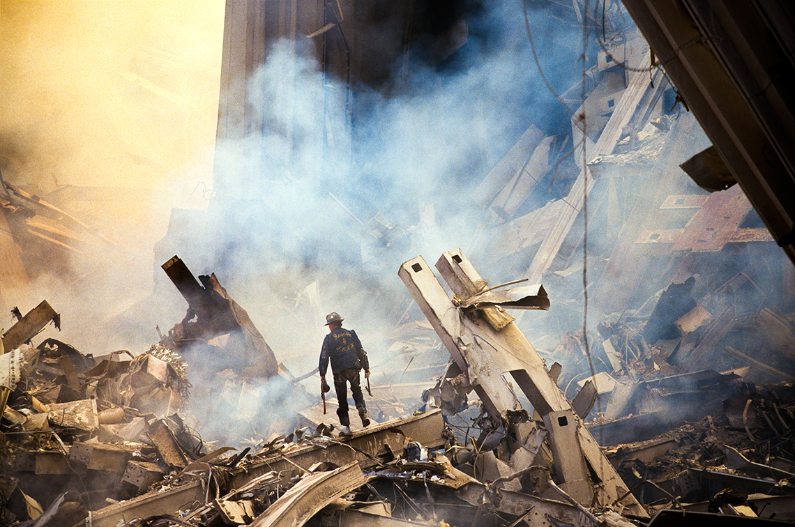 a lone first responder is dwarfed by the rubble of the world trade center after the september eleventh attack