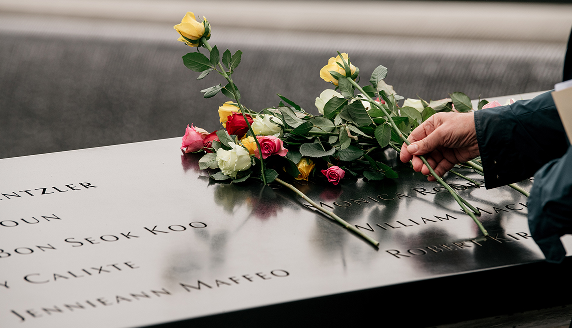 A person puts flowers on a memorial