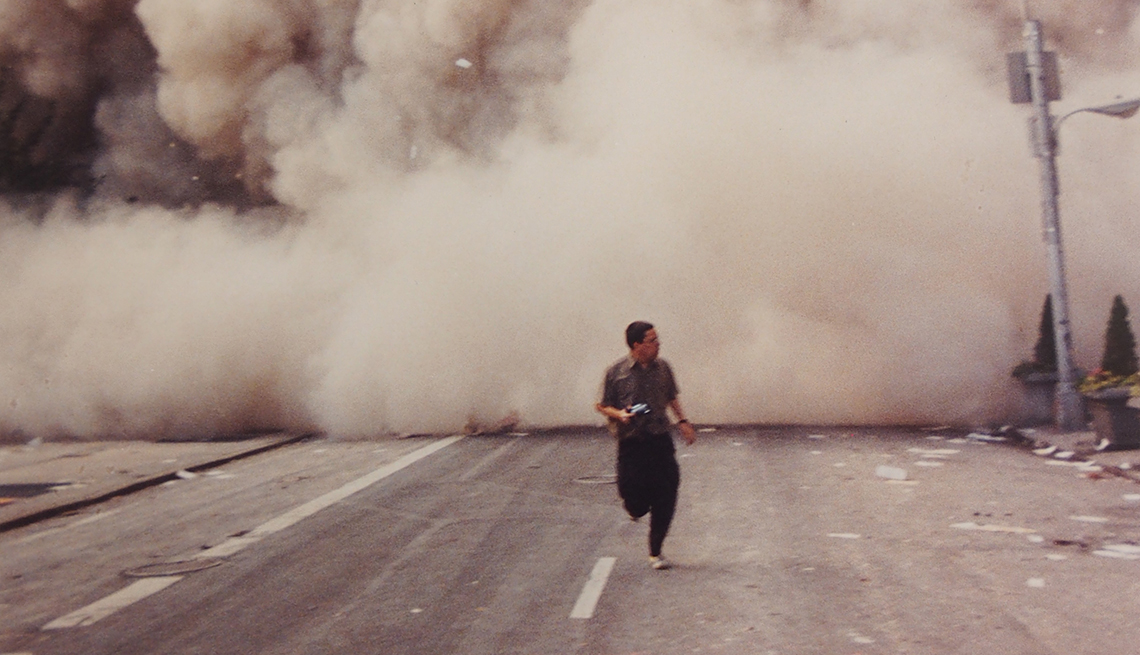 editor george mannes runs from the twin towers in new york city on september eleventh surrounded by a huge dust cloud