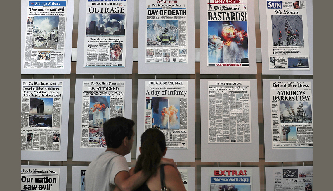 two museum visitors stand in front of a wall of newspapers from all over the world with the headlines of the nine eleven terror attacks at the newseum in washington d c in two thousand sixteen