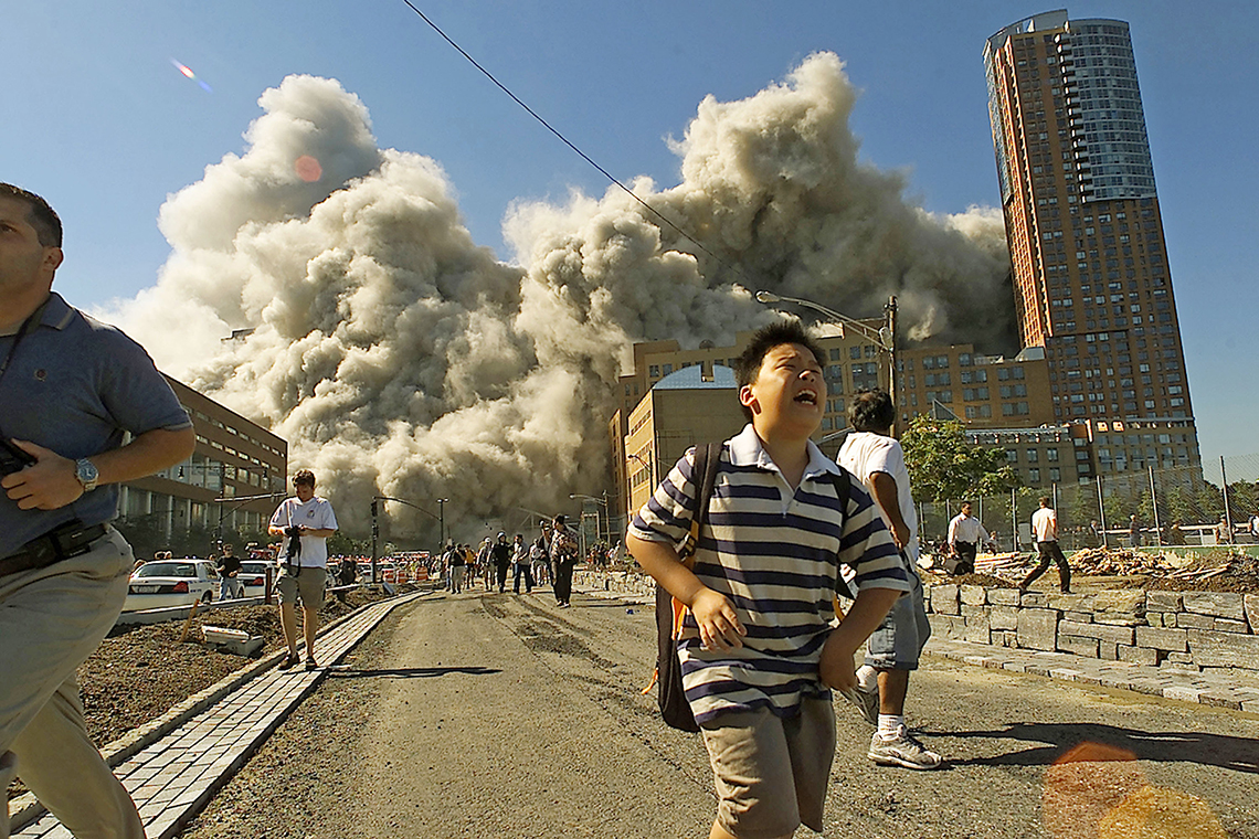 people running away as the second tower of the world trade center collapses in the distance