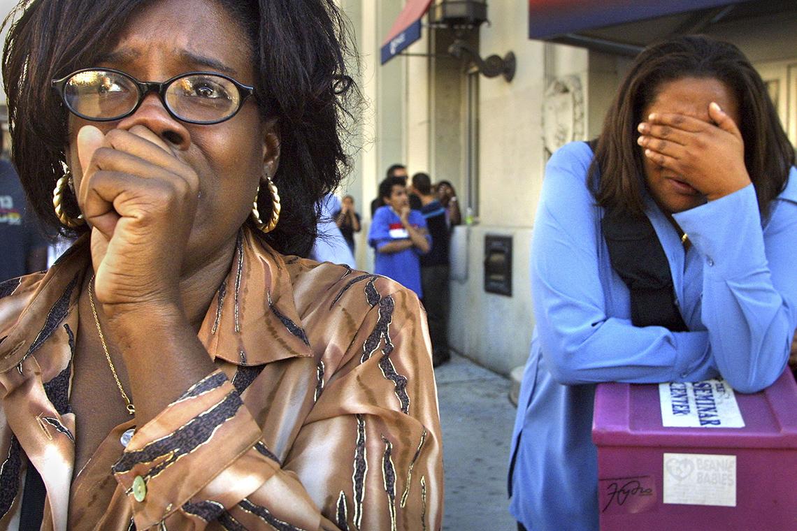 Dos mujeres reaccionan en la ciudad de Nueva York: una se cubre la boca con horror y la otra se cubre los ojos