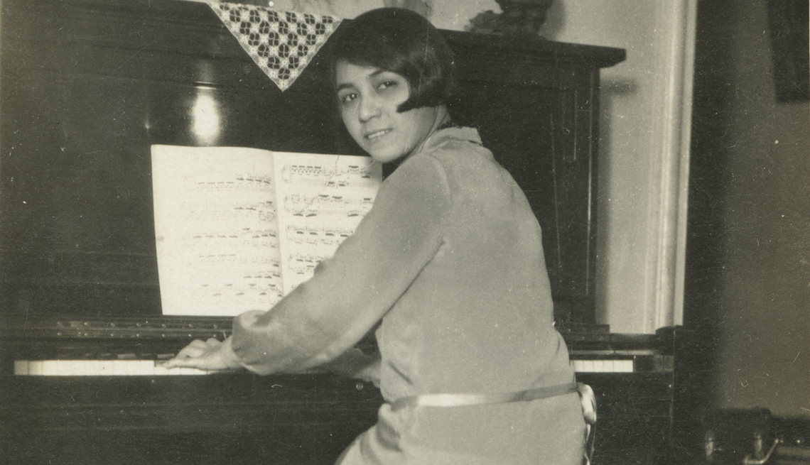 Clotilde Arias sitting at the piano in her Brooklyn, New York apartment