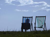 AARP recommends a checklist of things to do when a loved one dies- a woman sits alone in a lawn chair next to an empty chair