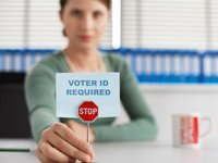 Voter ID Laws can restrict older voters, Woman in an office holding a little stop-sign and paper that reads Voter ID Required