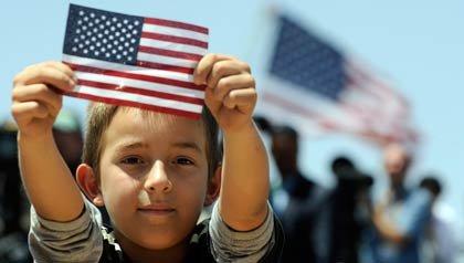 El presidente Barack Obama habla sobre la inmigración en el Chamizal National Memorial en El Paso, Texas, mientras un niño muestra una bandera de los EE.UU.
