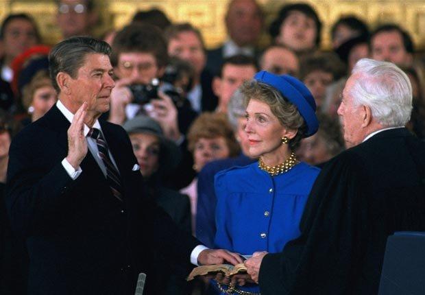 Primera Dama Nancy Reagan observa mientras el presidente Ronald Reagan jura su cargo durante la ceremonia en la Rotonda bajo la cúpula del Capitolio en Washington Lunes, 21 de enero 1985. - Discursos de inauguración