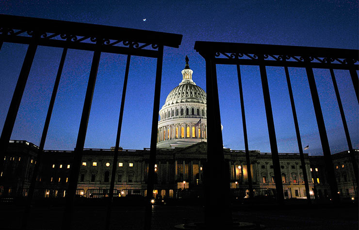 The US Capitol Building seen through a fence at night. How a government shutdown could impact you.