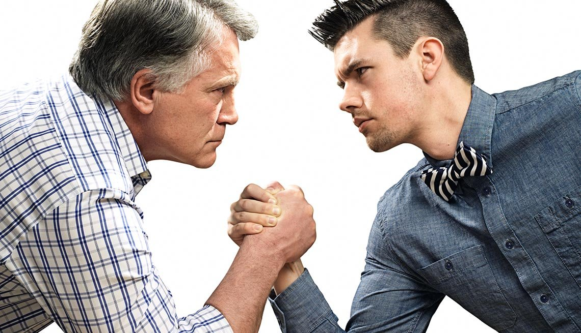 An older and younger man arm wrestle,  inter-generational war