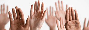 Closeup Of Raised Multiethnic Hands, find out more AARP Voter Guide
