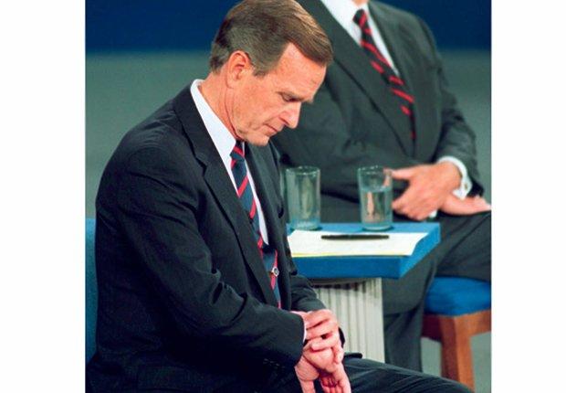 Presidente George H.W. Bush mirando su reloj durante un debate político