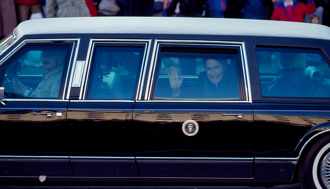 Presidente George H. W. Bush, saluda desde el auto presidencial