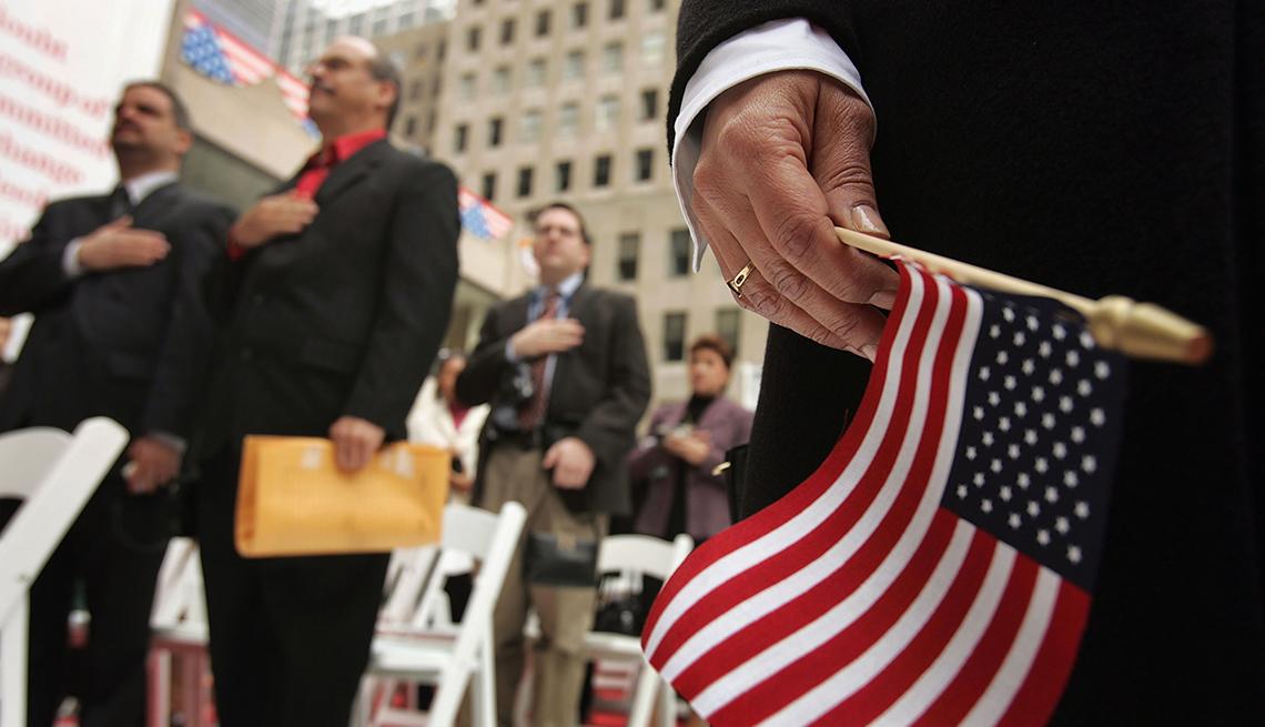 Mano sosteniendo una bandera americana con personas detrás jurando como ciudadanos