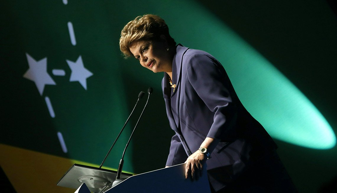 Dilma Rousseff waist length tilted making a speech with green background with white stars and dashes