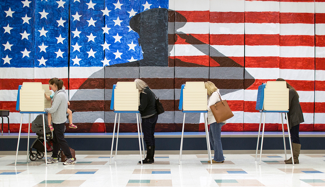 People vote in front of an American flag