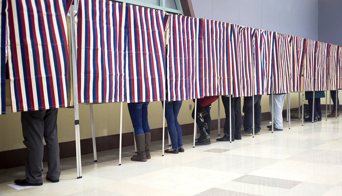 people voting in polling place with American flag stiped curtains