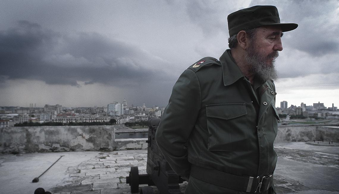 Fidel Castro vestido con uniforme militar de espaldas a un cielo nublado y con edificios detrás de él