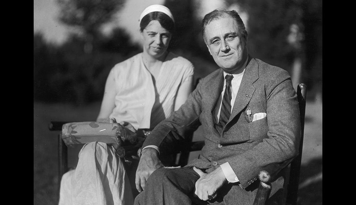 Franklin Delano Roosevelt sentado en una silla de ruedas, sonriendo y al lado de su esposa Eleanor quien lleva un vestido blanco y sombrero