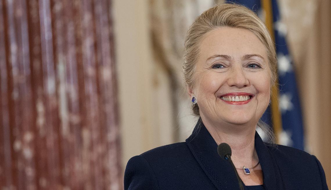Portrato de Hillary Clinton sonriendo, con cortinas y bandera de USA detrás de ella