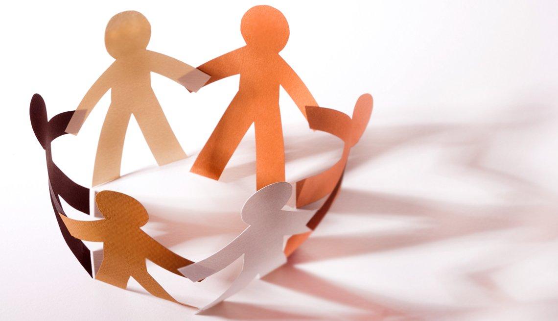Figuras de papel recortadas en forma de personas agarradas de la mano haciendo una ronda