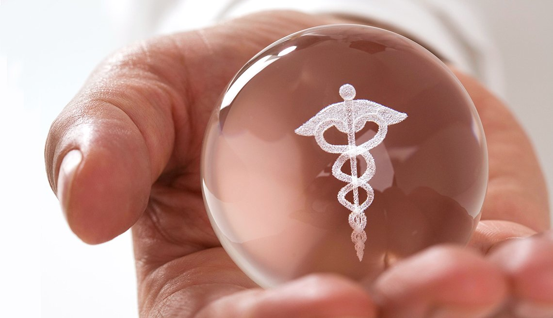 a hand holds a glass ball with a caduceus on it.