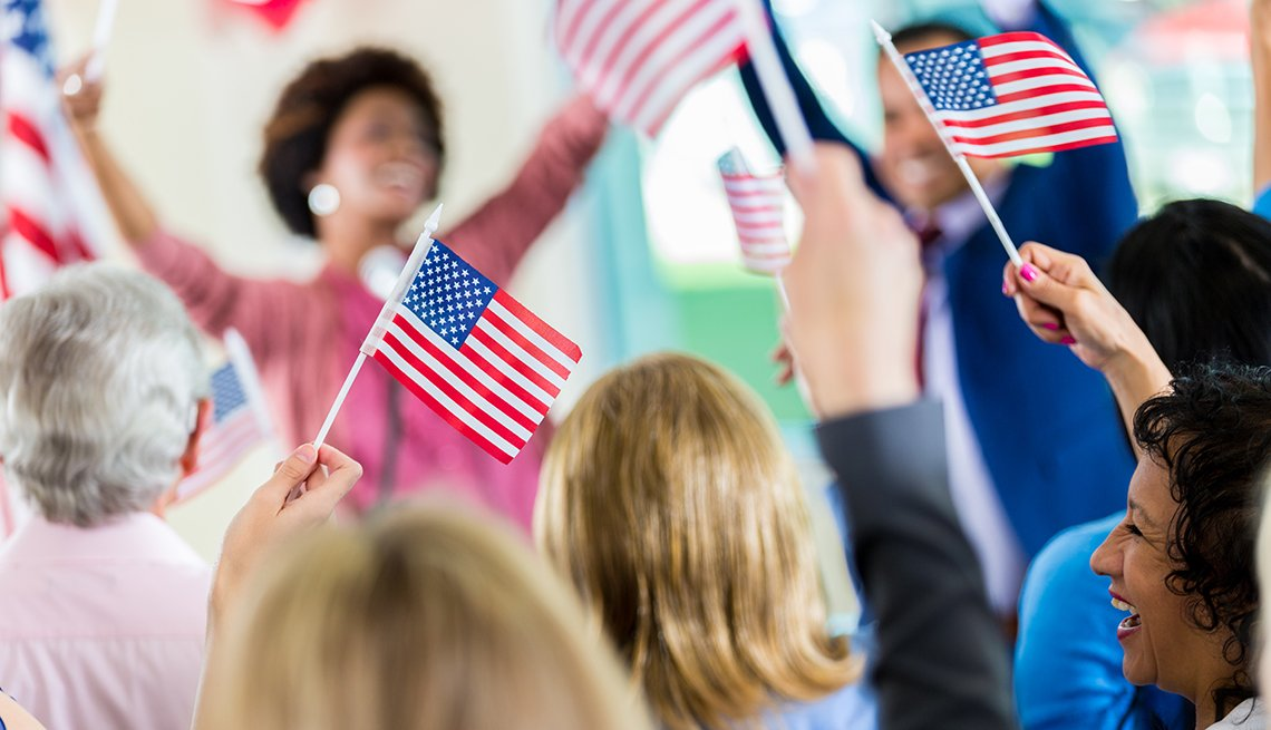 Personas agitan banderas de Estados Unidos con la mano