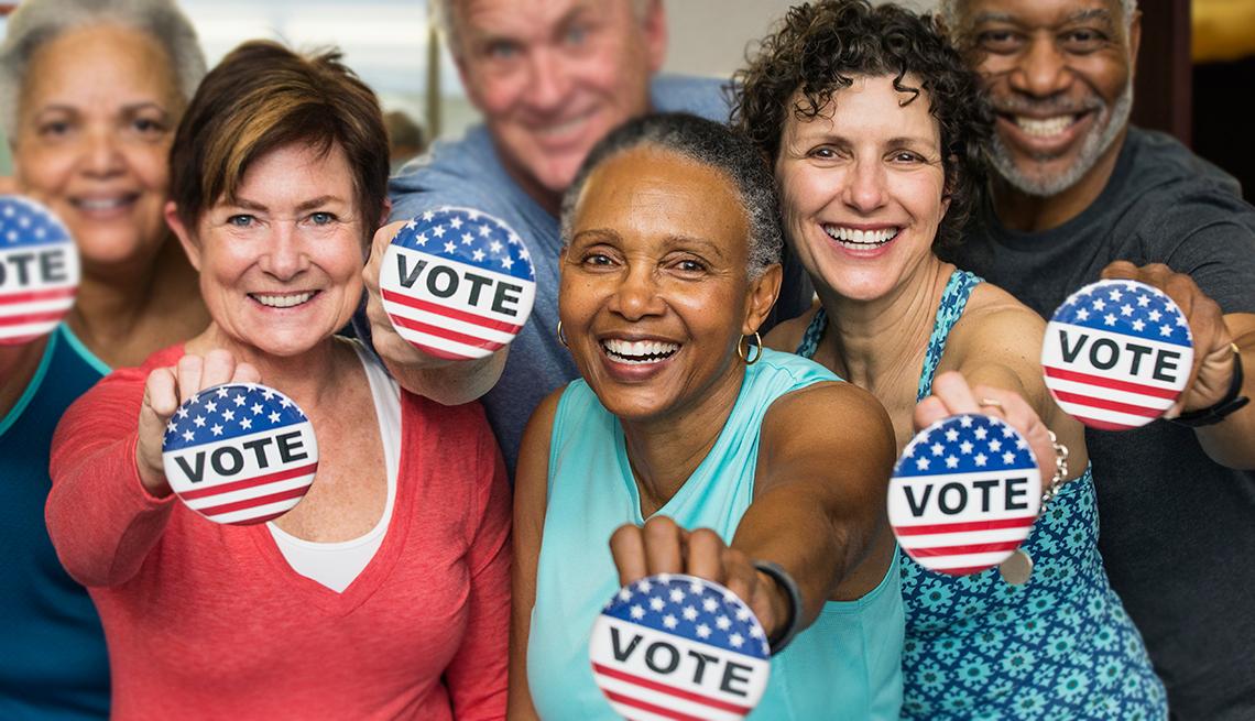 Votantes mayores sostienen en la mano botones que dicen -Vote-