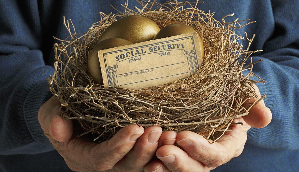 Un hombre mayor sostiene un nido que contiene dos huevos de oro y una tarjeta del Seguro Social en blanco.