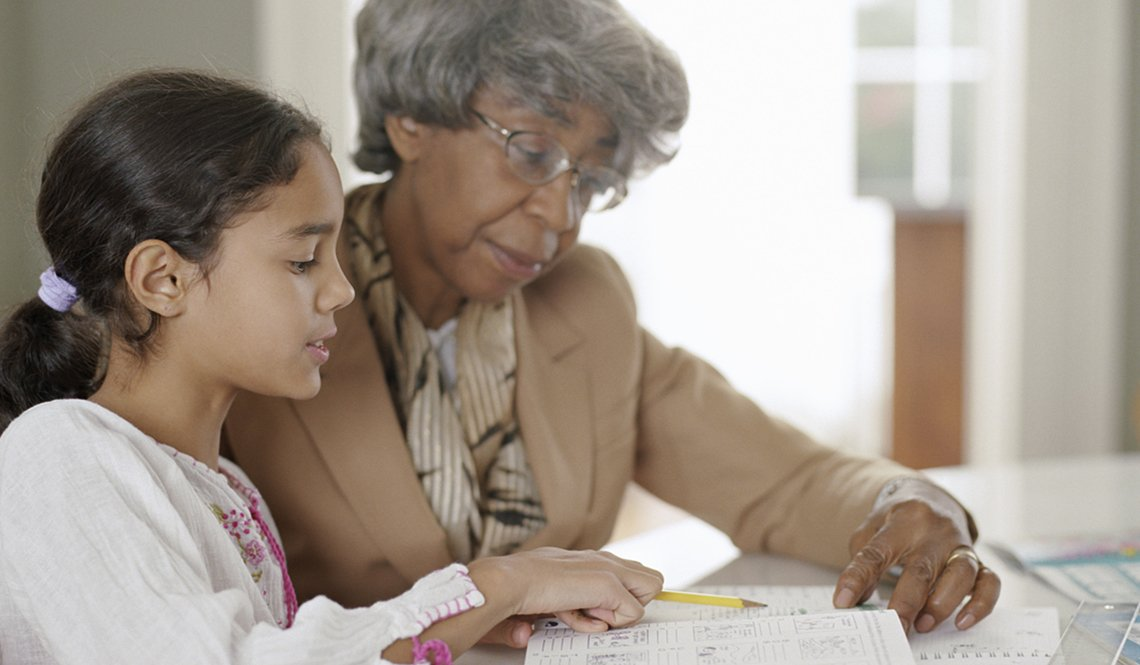 Grandmother helps her granddaughter with homework