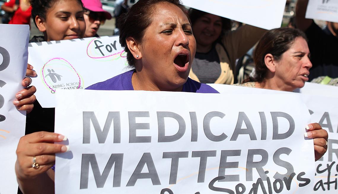 Mujeres con carteles protestan por el bienestar de Medicaid.