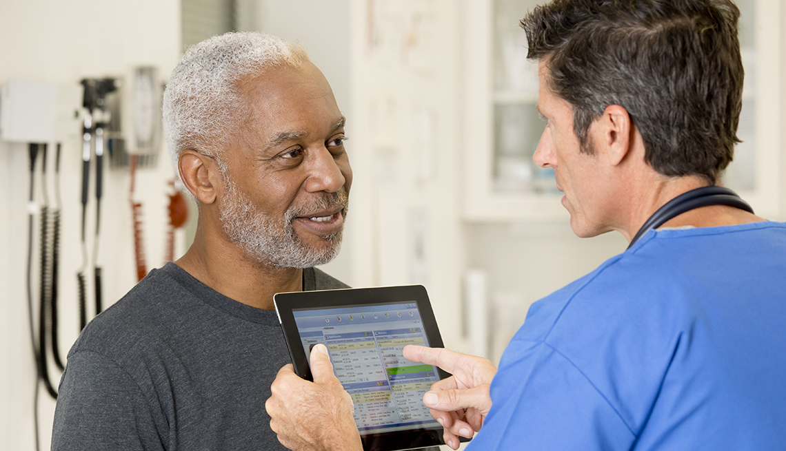 Enfermero habla con un paciente en un consultorio médico.