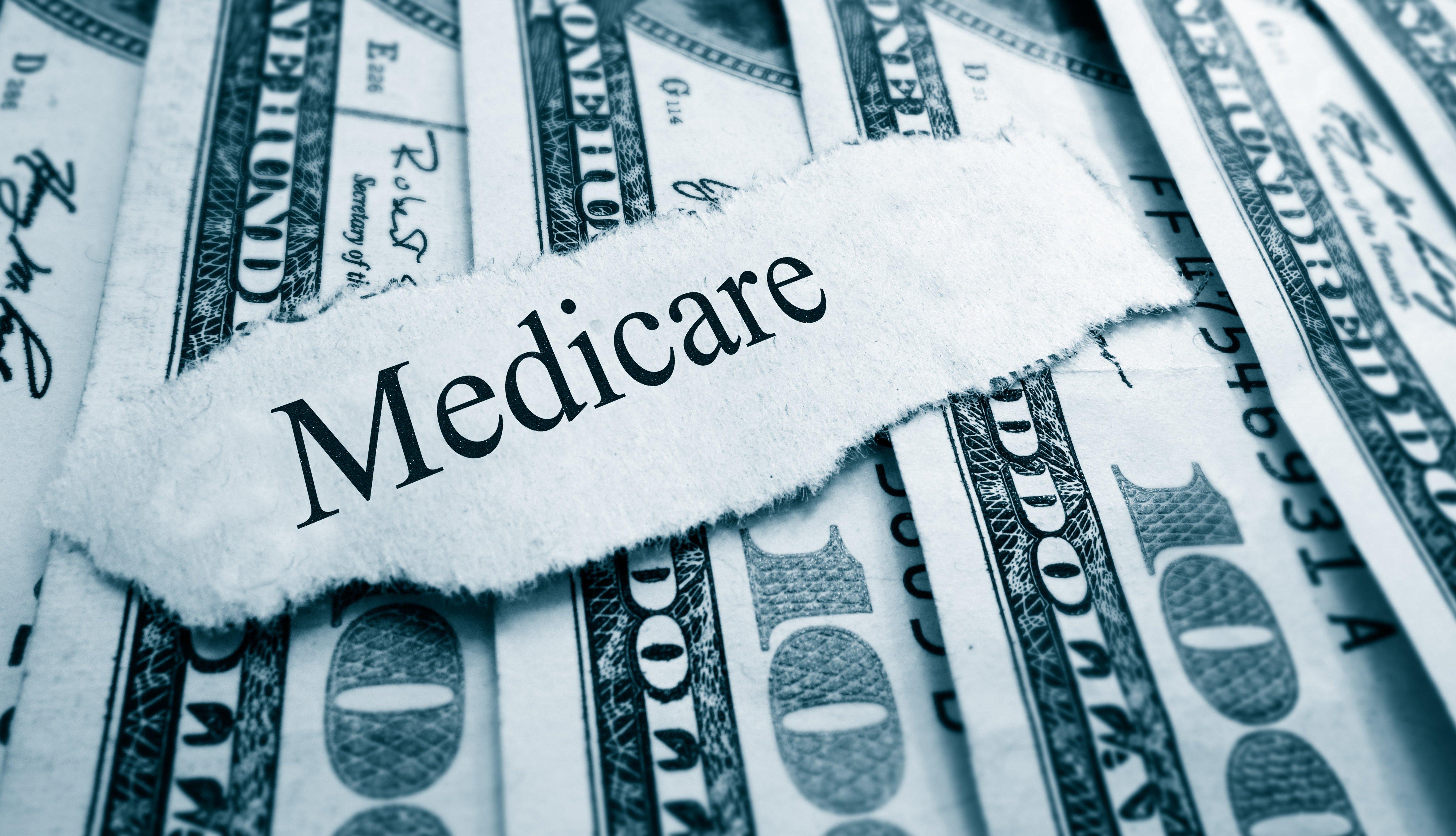 Medicare escrito en trozo de papel sobre billetes de cien dólares