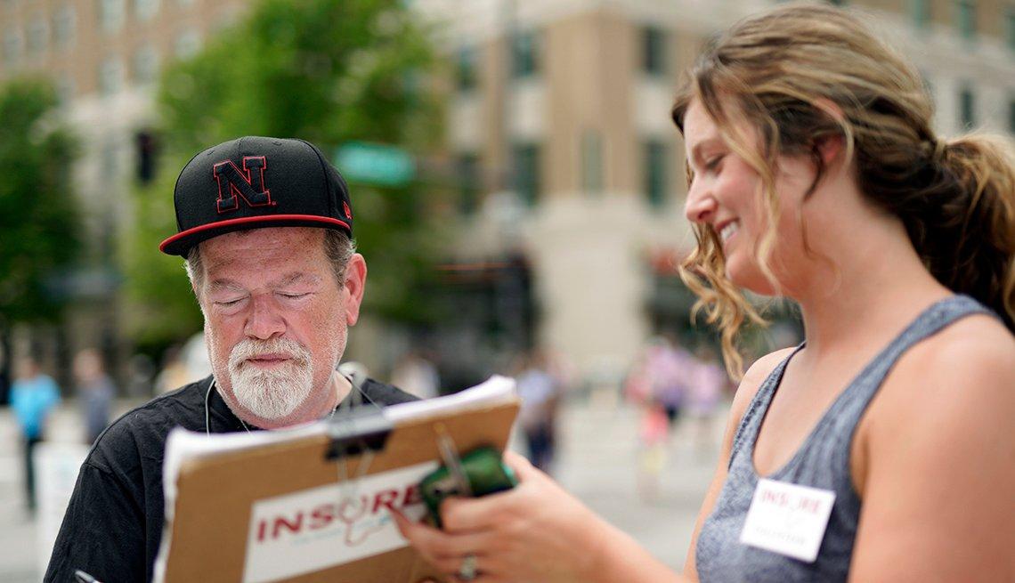 Una voluntaria política, a la derecha, recluta a un hombre para firmar una petición legislativa.
