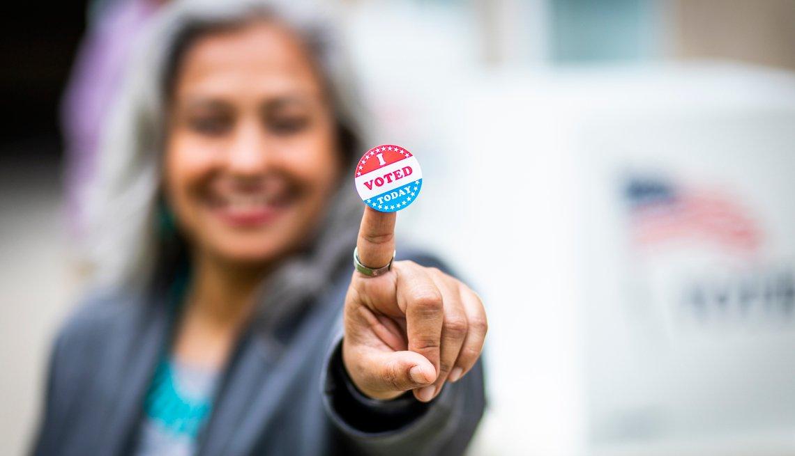 Mujer mayor muestra una calcomanía tras haber votado en las elecciones.