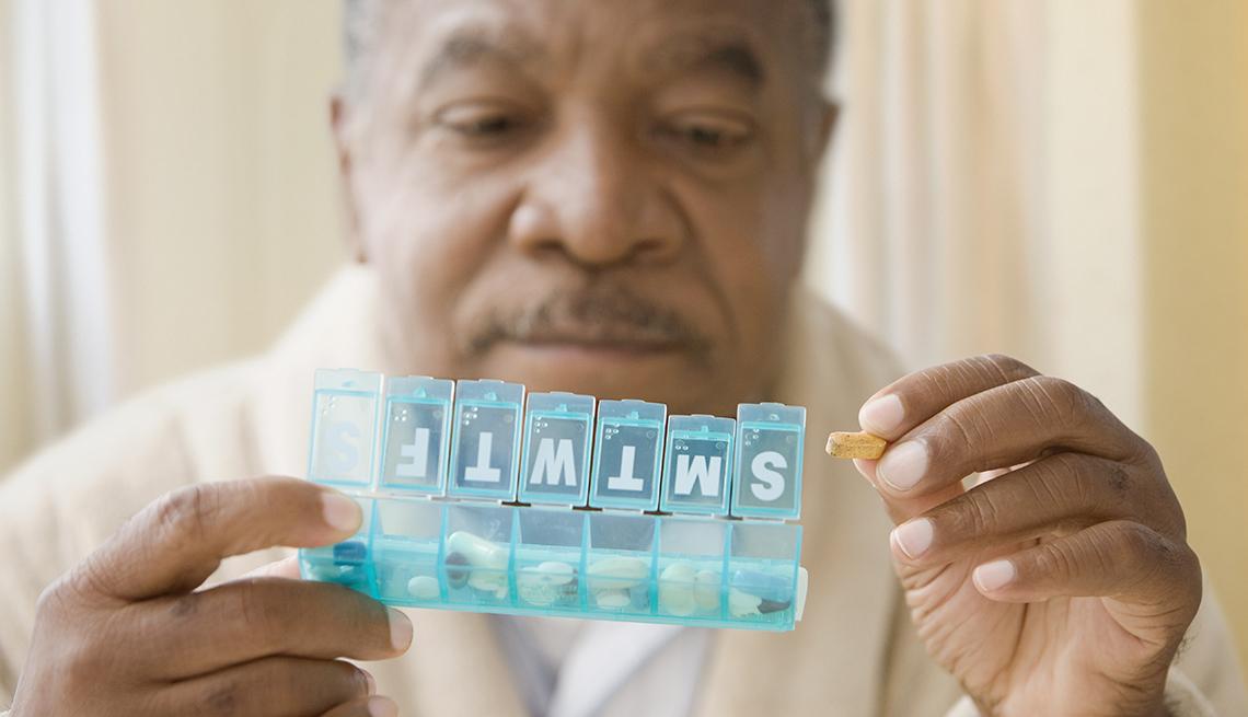 Hombre observa su pastillero semanal.