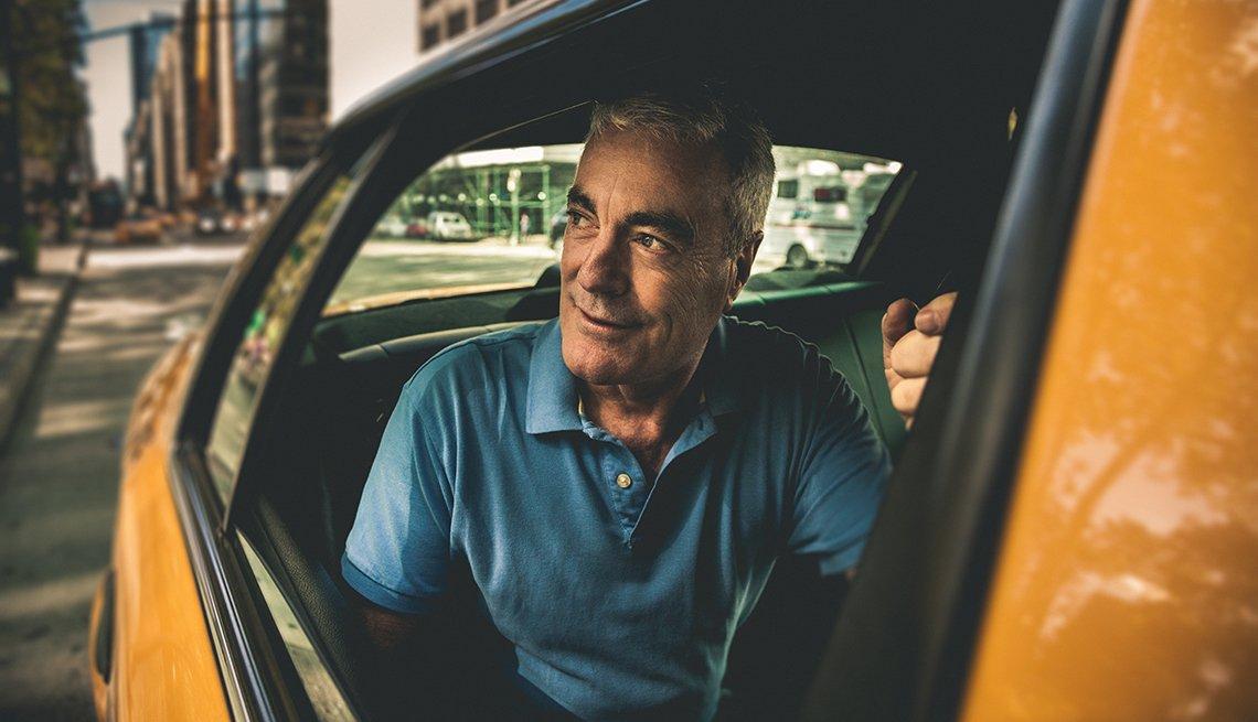 Hombre mayor va en un taxi.