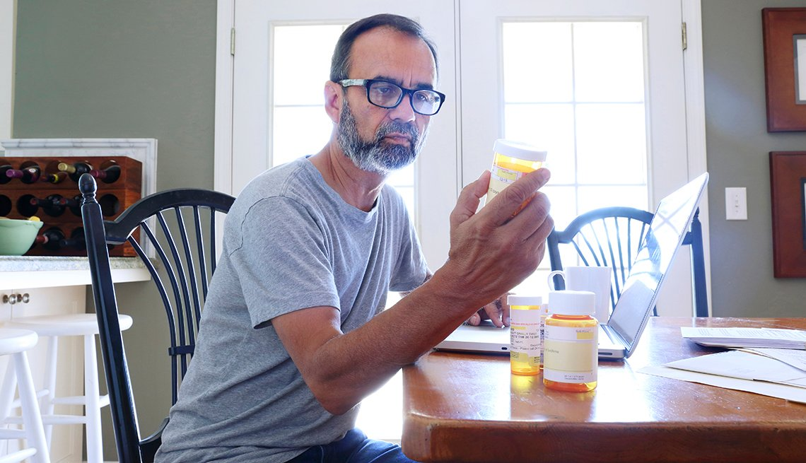 Man looking at a bottle of pills at a table