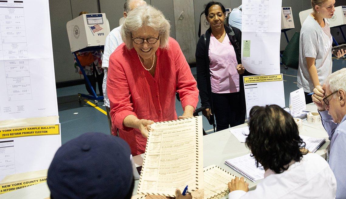 Mujer mayor recibe unos documentos mientras se alista a votar en las elecciones de mitad de mandato de 2018.