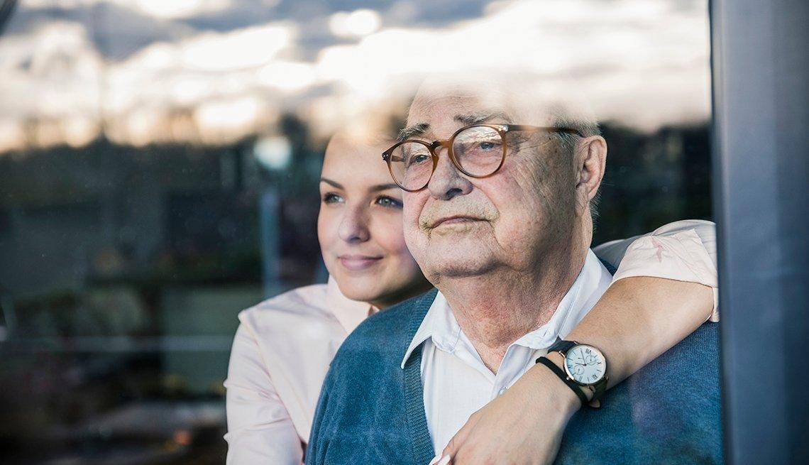 Mujer joven abrazando a un hombre mayor
