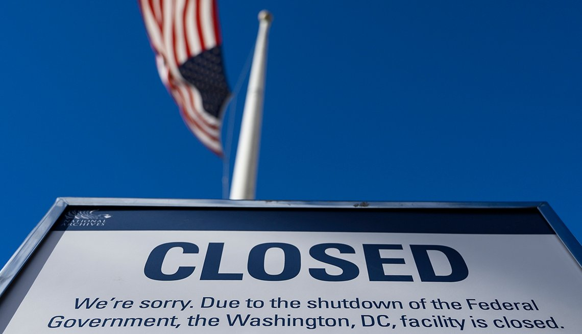 A sign that says closed with the American flag flying above it